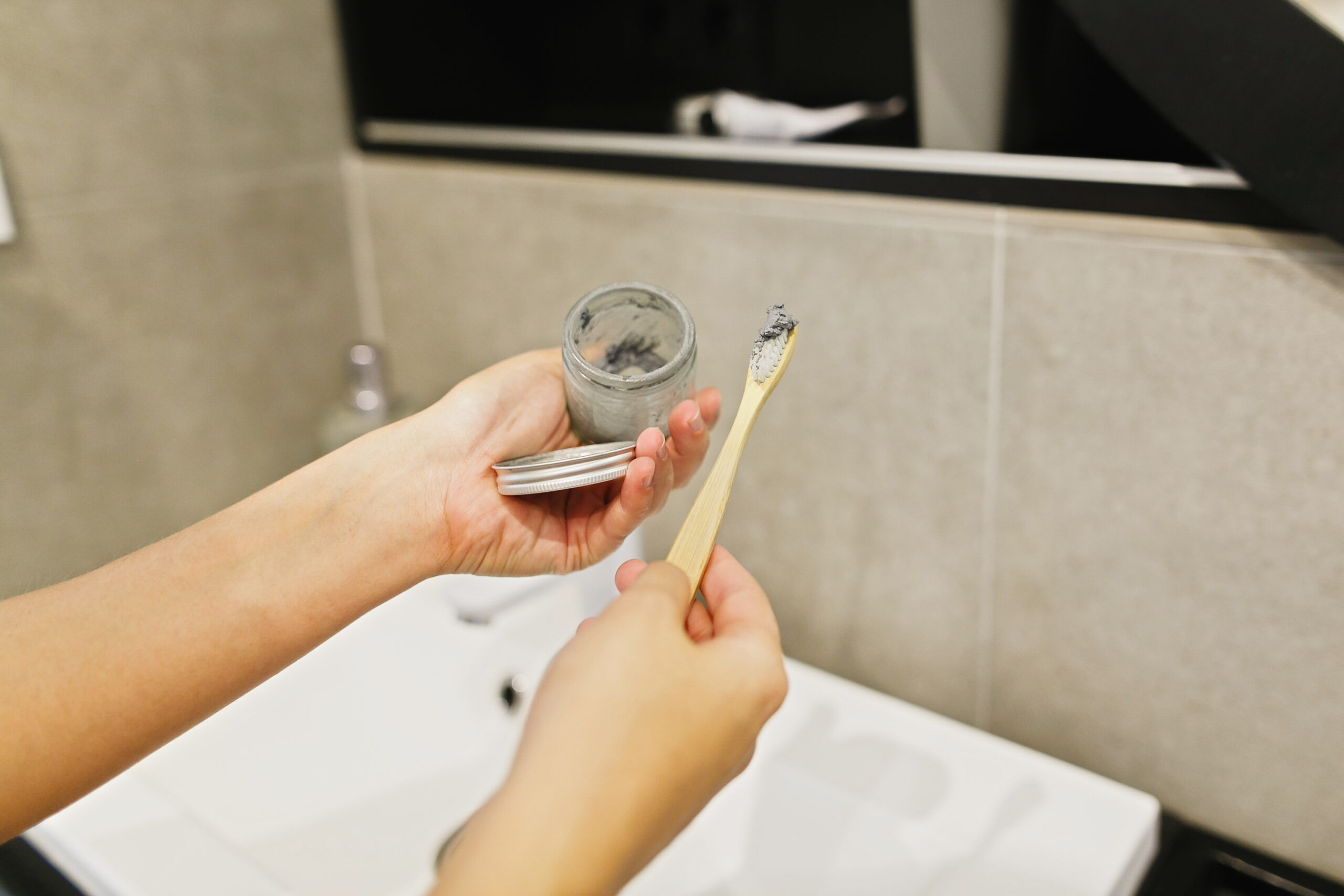 Woman using charcoal toothbrush and charcoal toothpaste